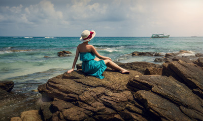 A girl in a hat sits on a rock. A girl on the rocks by the sea.
