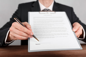 Businessman indicates the place for signing in the contract,which is attached to a clipboard.