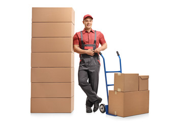 Mover with a hand truck leaning on a stack of boxes and smiling