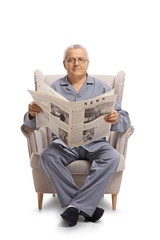Mature man seated in an armchair holding a newspaper and looking at the camera