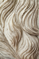 Human hair or animal fur curly waves carved in stone.  White marble sculpture detail background