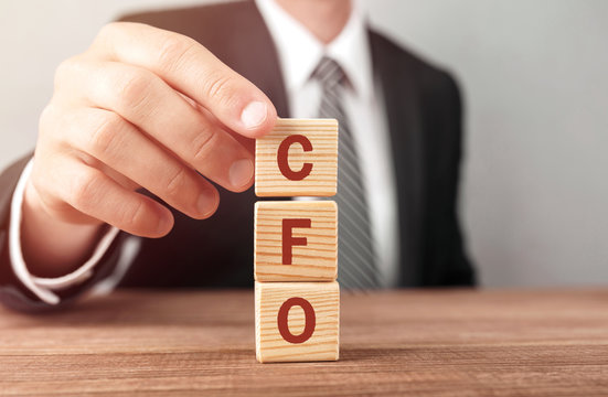 Businessman made word CFO with wood building blocks.