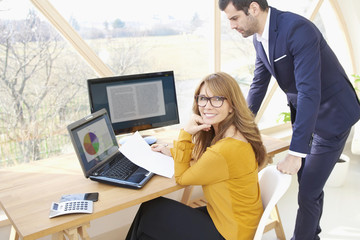 Executive businesswoman and young financial assistant businessman working together at office