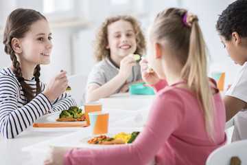 Smiling girl eating vegetables during lunch break with friends at school