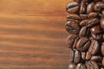 Selected coffee roasted beans are lying on a wooden background.