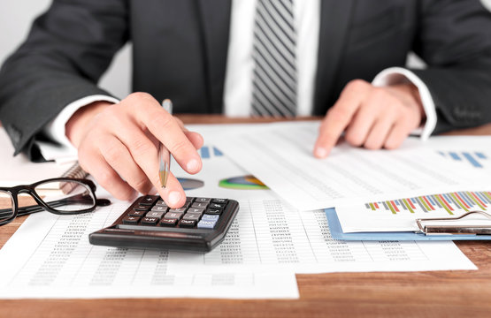 Businessman working with using a calculator to calculate the numbers. Finance accounting concept
