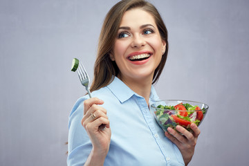 Happy woman eating salad looking at side.