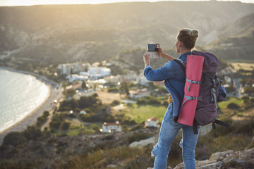 Focus on female person standing with her back and taking picture of coastline from high. She is carrying rucksack behind. Copy space in left side
