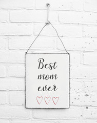 White square metal plate on white bricks background - with text happy mothers day for the mom dad in de world and red hearts - celebration - mock up - template