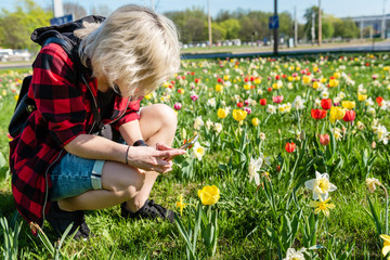 A young woman is photographing flowers by her smartphone. Spring concept