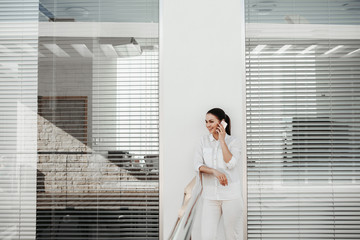 Portrait of laughing female person standing on balcony and using gadget for communication. Office blinds on background. Copy space in left side