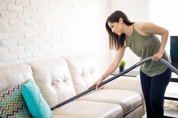 Busy woman cleaning sofa with vacuum cleaner