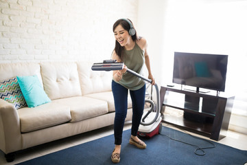 Delighted woman enjoying music and singing with headphones and vacuum cleaner