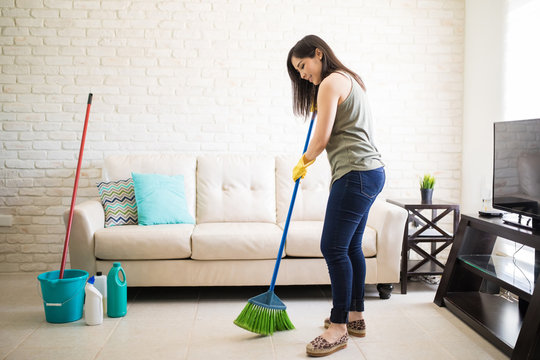 Woman sweeping floor feeling happy