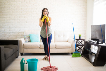 Young woman standing with mop and looking at camera.