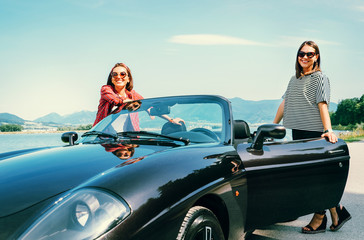 Two female freinds traveling by cabriolet