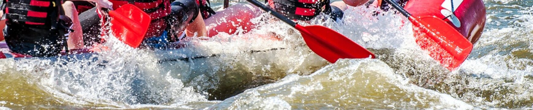 Rafting, kayaking. Extreme sport. Water ecological tourism. Close-up view of oars with splashing water.