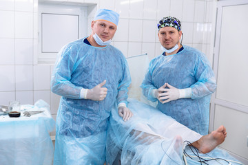 A team of doctors in sterile medical gowns perform surgery in a surgical room. Surgeon with an assistant after the procedures. Portrait of medical workers.