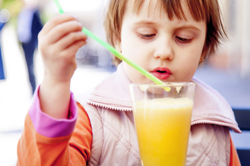 Little cute girl drinking tasty natural smoothie juice outdoors. (children's food, healthy lifestyle, vitamins concept)