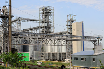 Part of modern working sugar plant (sugar refinery, factory), special metal equipment around, large metal tanks in the background, blue sky