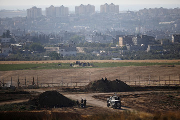 Israeli soldiers and military vehicles are seen on the Israeli side of the border fence between Israel and the Gaza Strip