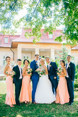 Cheerful & fun groom with bride, bridesmaids & groomsmen posing outdoors. Newlywed couple with best friends make funny photo near old castle.