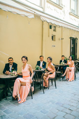 Happy fun newlyweds posing in street with bridesmaids & groomsmen. Bride with groom sitting at street cafe outdoor.