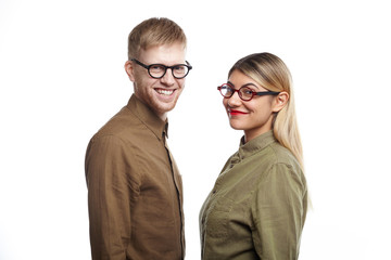 Confident successful team of two young ambitious business partners male and female posing at white wall and looking at camera with cheerful smiles, happy with good results of their common project