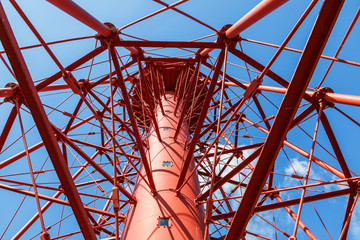 Red cast iron lighthouse against a blue sky from below
