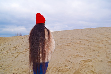 Rear view beautiful long hair girl in the desert in nature.