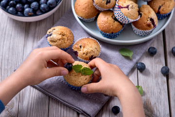 Child´s hands decorating blueberry muffins, healthy homemade dessert with berries