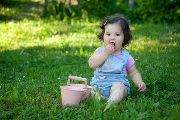 Baby girl eating summer raspberries. Sitting in the grass, enjoying the nature. Childhood, People, Children