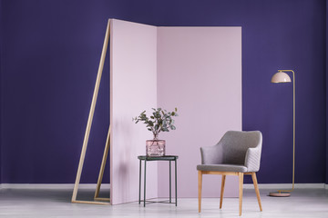Real photo of twigs in a pink, glass vase on a metal table next to a gray armchair in cozy, pastel interior