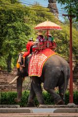 Thailändischer Elefant mit reitenden Touristen auf Straße vor den Ruinen von Ayutthaya