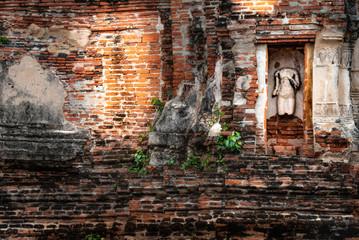 Siamesische Ruinenstadt Ayutthaya: Alte Mauer mit kopflosem Torso in Wandnische