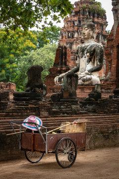 Siamesische Ruinenstadt Ayutthaya, Wat Mahathat: Buddha-Statue mit Karren, Besen und buntem Hut