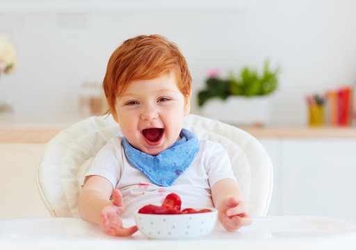 portrait of happy toddler baby eating tasty fresh starwberries