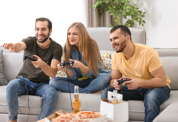Young people playing video games at home