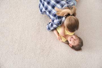 Cute little girl and her mother lying on cozy carpet at home