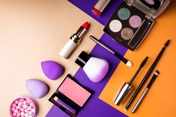 Makeup products and decorative cosmetics on color background flat lay. Fashion and beauty blogging concept. Top view, copy space