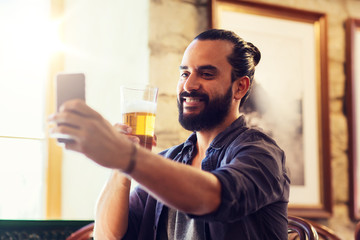 people and technology concept - man with smartphone drinking beer and taking selfie at bar or pub
