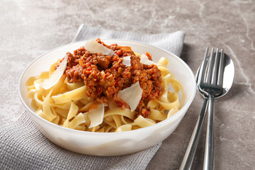 Plate with delicious pasta bolognese on table