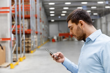 wholesale, logistic business, technology and people concept - businessman with smartphone at warehouse