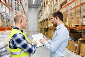 wholesale, logistic business and people concept - manual worker and businessman with clipboards at warehouse