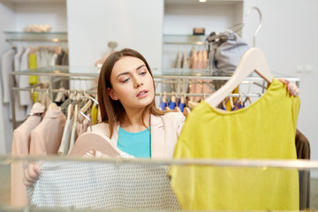 shopping, fashion, sale and people concept - young woman choosing clothes in mall or clothing store
