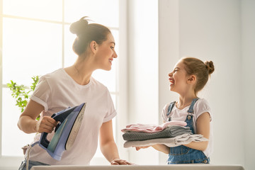 mother and daughter ironing at home
