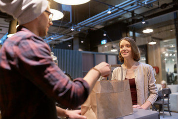 small business, takeaway food, people and service concept - man or seller giving paper bag and money change to happy female customer at vegan cafe