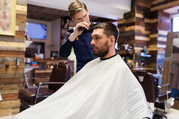grooming, hairdressing and people concept - man and barber with comb and scissors cutting hair at barbershop