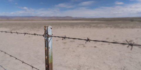 Barb wire fence in the dry desert country with metal post