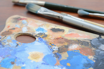 Artist's palette with colorful oil paint strokes and paintbrushes